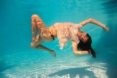 在游泳池的妇女undewater 免版税库存照片