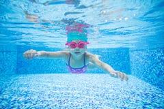 在游泳池的小女孩潜水 免版税库存照片