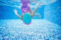 在游泳池的小女孩潜水 免版税图库摄影