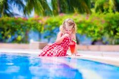 在游泳池的小女孩饮用的汁液 库存图片
