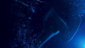 在游泳池的年轻孕妇游泳在与照明的晚上 做锻炼的蓝色泳装的女孩 影视素材