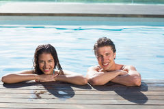 在游泳池的微笑的年轻夫妇 库存图片