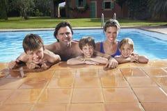 在游泳池的愉快的家庭 库存图片