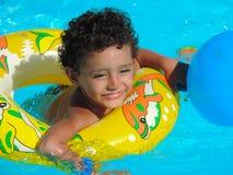 在游泳池的愉快的男孩戏剧 库存图片