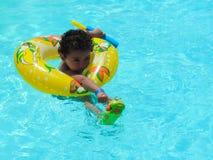 在游泳池的愉快的男孩戏剧 库存照片
