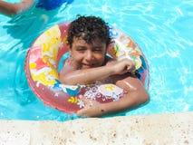 在游泳池的愉快的男孩戏剧 免版税库存图片