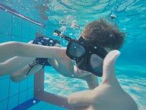 在游泳池的水下的年轻男孩乐趣与风镜 暑假乐趣 图库摄影