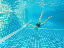 在游泳池的水下的年轻男孩乐趣与风镜 暑假乐趣 免版税库存图片