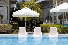 在游泳池的白色太阳床为在美好的summe放松 免版税库存照片
