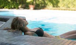 在游泳池的美好的性感的妇女休息 免版税库存照片