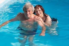在游泳池的资深夫妇 免版税库存照片