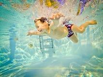 在游泳池的水下的年轻男孩乐趣与大微笑假期乐趣 免版税库存图片