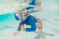 在游泳池的水下的年轻男孩乐趣与废气管 暑假乐趣 免版税库存照片