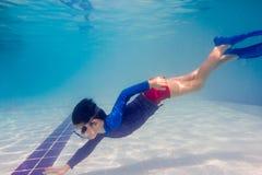 在游泳池的水下的年轻男孩乐趣与风镜 暑假乐趣 库存图片