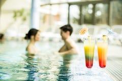 在游泳池的年轻夫妇 免版税库存图片