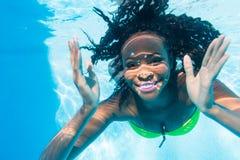 在游泳池的黑女孩潜水假期 库存照片