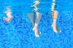 在游泳池的滑稽的水下的家庭腿 免版税库存照片