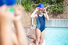 在游泳池边的小女孩佩带的游泳凝视 免版税库存照片