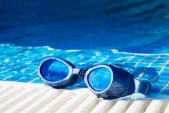 在游泳池边的游泳池风镜 免版税库存图片