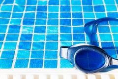 在游泳池边的游泳池风镜 图库摄影