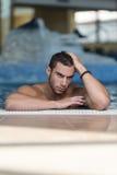 在游泳池边缘放松的人休息  免版税库存照片