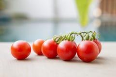 在游泳池边缘的特写镜头新鲜的红色蕃茄 免版税库存图片