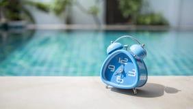 在游泳池边缘的蓝色时钟 库存照片