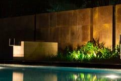 在游泳池边附近的夜风景有新的花岗岩瓦片砖块的 库存照片