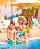 在游泳池边附近的大家庭 免版税库存照片