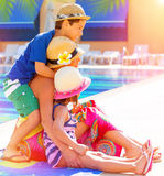在游泳池边附近的愉快的家庭 免版税库存图片