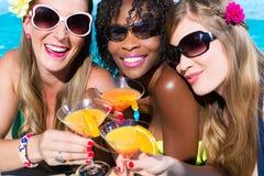 在游泳池酒吧的朋友饮用的鸡尾酒 库存图片