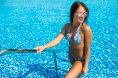 在游泳池里面的Sexywoman画象佩带的比基尼泳装享受夏天职业 免版税库存图片