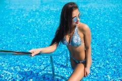 在游泳池里面的Sexywoman画象佩带的比基尼泳装享受夏天职业 免版税图库摄影