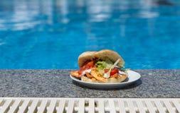 在游泳池附近的三明治 库存图片