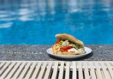 在游泳池附近的三明治 图库摄影