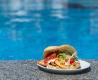 在游泳池附近的三明治 库存照片