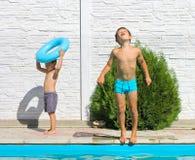 在游泳池附近的两个兄弟 库存图片