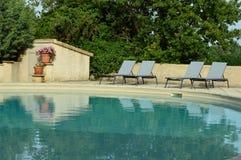 在游泳池附近的松弛椅子 免版税库存照片