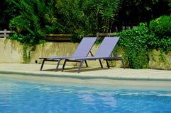 在游泳池附近的松弛椅子 免版税库存图片