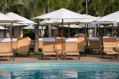 在游泳池附近的海滩睡椅在热带手段,泰国 免版税库存照片