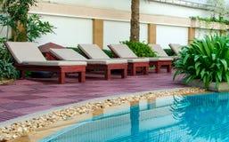 在游泳池附近的海滩睡椅在热带手段 免版税库存图片