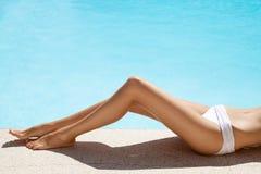 在游泳池附近的美好的妇女腿 免版税库存图片