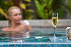在游泳池附近的香宾在一名美丽的妇女的背景 库存照片