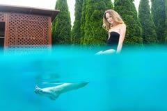 在游泳池附近的年轻美丽的妇女 免版税库存图片