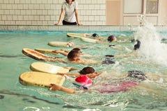 在游泳的技能教训内的小学孩子 免版税库存照片