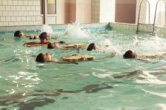 在游泳的技能教训内的小学孩子 库存照片