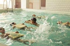 在游泳的技能教训内的小学孩子 库存图片