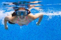 在游泳的画象年轻微笑的妇女游泳undewater 库存照片