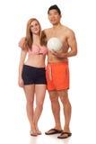在游泳衣的新夫妇与排球 免版税图库摄影