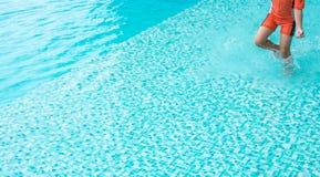 在游泳水池的男孩奔跑 免版税库存图片